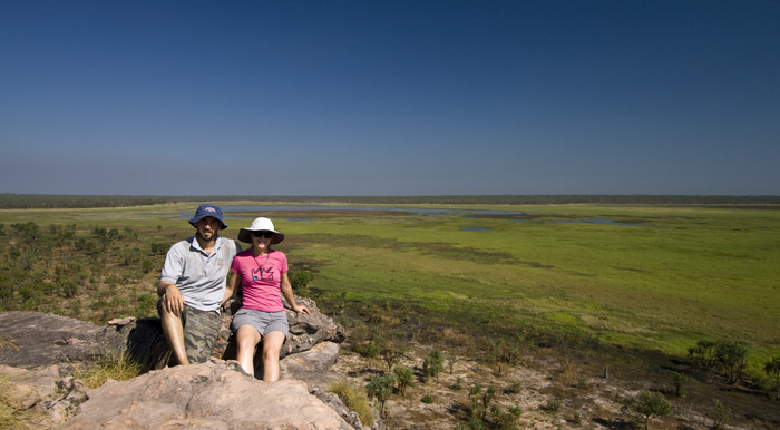 Sam and Lisa on the edge of the sandstone escarpment with wetlands below at the Ubirr Aboriginal art site