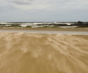 Powerful seas and wisps of flying sand at the mouth of the Pieman River