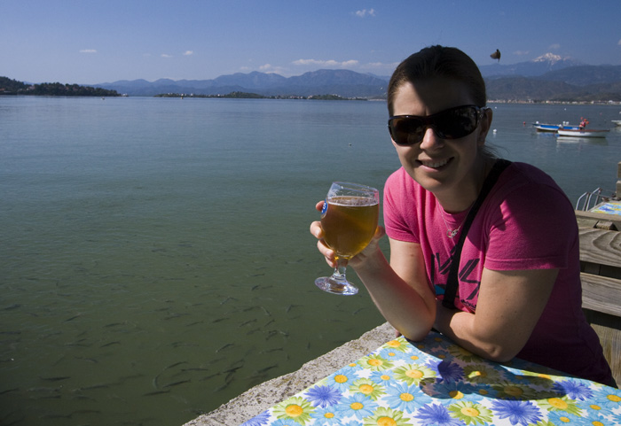 Lisa knocking back an Efes with bread-hungry fish in the water behind her