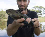 Sam and an Eastern Water Dragon on the banks of the Snowy River