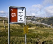 Signs on the way to Derrick Hut with Mount Hotham village in the distance