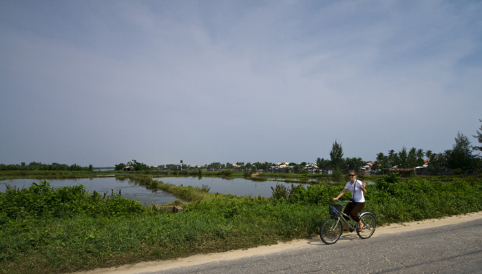 Lisa riding her bike next to the rice paddies between Hoi An and Cua Dai Beach