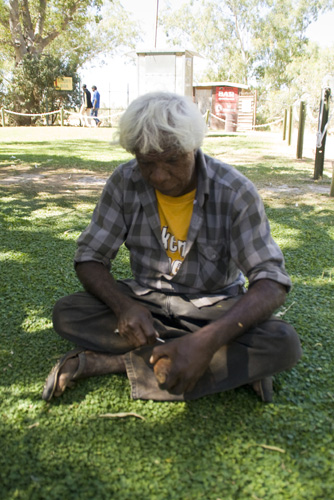 An Aboriginal in Fitzroy Crossing carving a Boab nut
