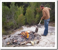 Sam tending to the fire by the Lindsay River